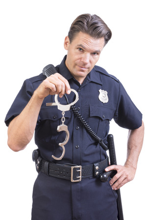 restraints: Handsome Caucasian police officer dangles pair of handcuff restraints in one hand as a warning on white background
