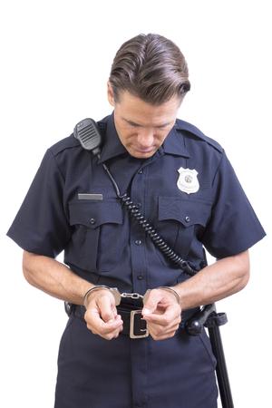Culpable oficial de policía de raza blanca con las muñecas esposadas y la cabeza hacia abajo en la vergüenza en el fondo blanco Foto de archivo