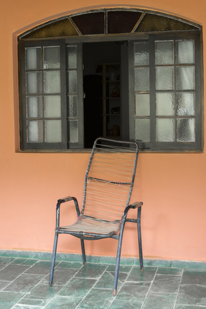 porch scene: Old plastic string bound chair on patio under rustic window of typical Brazilian country home