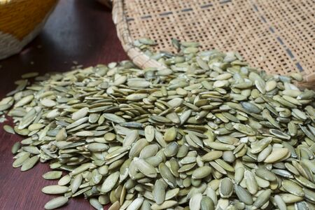 sifter: Closeup pile of fresh green pepitas pumpkin seeds on table with traditional reed sifter and basket