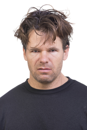 Portrait of scruffy Caucasian man with long messy hair and expression of disgust on white background