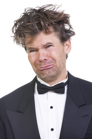 Portrait of pathetic crying Caucasian man with long messy hair wearing flashy black tuxedo on white background Stockfoto