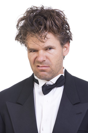Portrait of mad deranged Caucasian man with long messy hair wearing messed up black tuxedo on white background Stockfoto