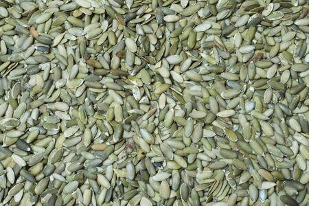 High angle shot of hundreds of fresh green pepitas pumpkin seeds filling camera frame