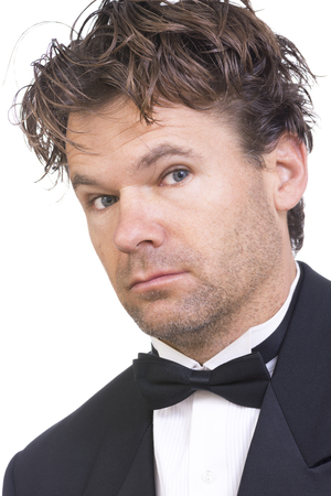 Closeup portrait of handsome unshaven Caucasian man with messy brown hair wearing black tuxedo on white background