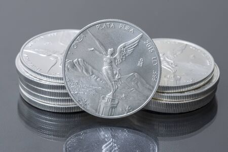 silver coins: Closeup of two small stacks and front of Mexican silver bullion coins on reflective surface