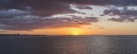 tampa bay: Beautiful panoramic of vivid orange sunrise under tinted gray clouds rising over highway 275 crossing Tampa Bay into Saint Petersburg observed from Tierra Verde Stock Photo