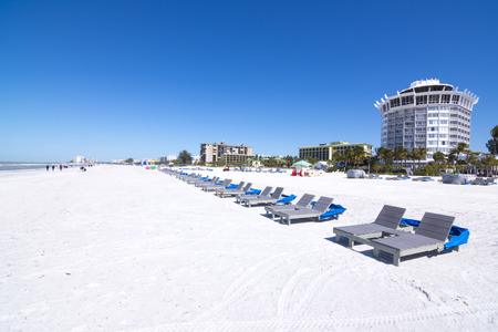 Resort and hotel lounge chairs lined up on clean, white sand under clear, blue sky at beautiful St. Pete Beach in St. Petersburg, Florida