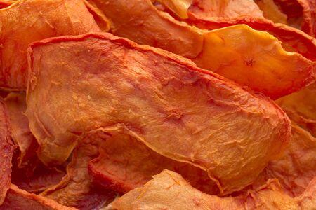 dehydrated: Macro closeup pile of thin sliced dehydrated orange papaya pieces