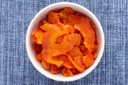 dried: High angle directly above bowl full of thin sliced dehydrated papaya on blue fabric placemat Stock Photo