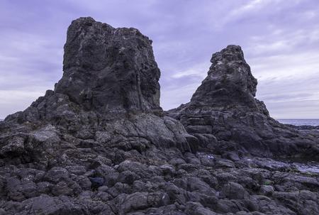 baja california: Two huge rocks tower above the sea at low tide on rocky coastline of Rosarito, Baja California, Mexico under moody cloudy grey sky Stock Photo