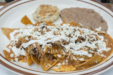 Fresh made Mexican chilaquiles with tortilla chips, shredded beef, salsa, and sour cream on a ceramic plate as a traditional breakfast