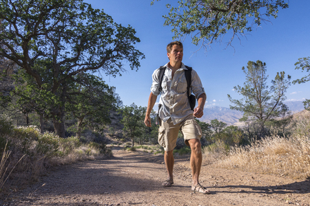 outdoorsman: Rugged Caucasian outdoorsman hikes with backpach and sandals on dirt road in California mountains