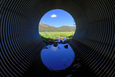 looking out: Interesting perspective from inside large corrugated metal drainage tube looking out upon beautiful grass meadow and mountains under sunny blue sky Stock Photo