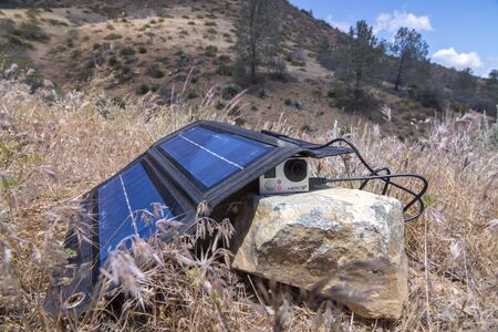 charger: LAKE ISABELLA, USA - MAY 24, 2016: When hiking or living off the grid a folding solar charger is a convenient way to keep small cameras and other devices powered up.