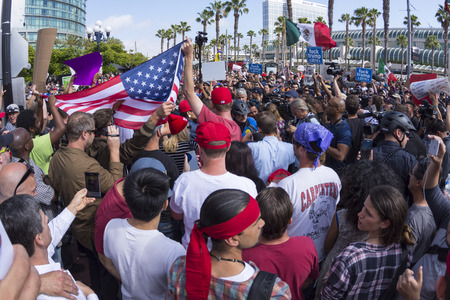 donald: SAN DIEGO, USA - MAY 27, 2016: Tensions rise as anti-Trump protesters meet Trump supporters and American and Mexican flags are held up representing each group at a Donald Trump rally at the San Diego Convention Center.