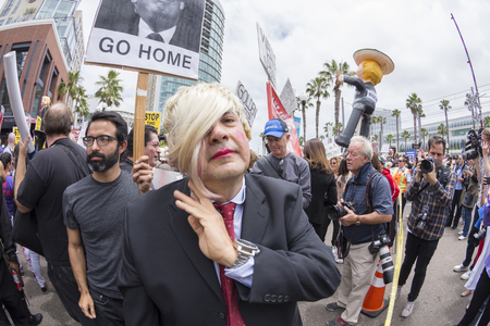 donald: SAN DIEGO, USA - MAY 27, 2016: An anti-Trump protester personifies Donald Trump by wearing a blonde wig and business suit amidst a crowd of demonstrators outside at Trump rally at the San Diego Convention Center