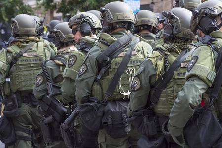 night stick: SAN DIEGO, USA - MAY 27, 2016: Riot police stand in formation ready to confront protesters at an anti-Trump rally at the San Diego Convention Center
