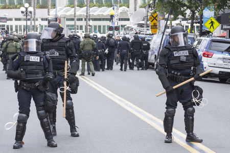 riot: SAN DIEGO, USA - MAY 27, 2016: Riot police in full tactical gear guard the street to the protest area outside a Trump rally in San Diego.