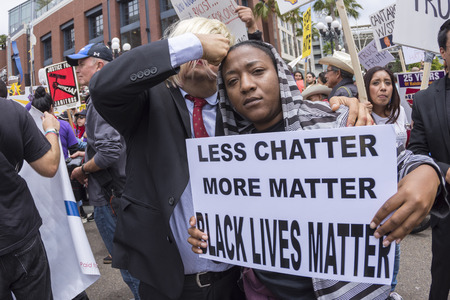 matters: SAN DIEGO, USA - MAY 27, 2016: A woman holds a Black Lives Matter sign while a Donald Trump impersonator pretends to hit her in the head with his fist at a protest outside a Trump rally in San Diego.