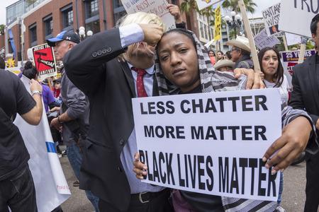 SAN DIEGO, Verenigde Staten - 27 mei 2016: Een vrouw houdt een zwarte Lives Matter teken terwijl een Donald Trump imitator doet alsof hij haar te slaan in het hoofd met zijn vuist bij een protest buiten een Trump rally in San Diego.