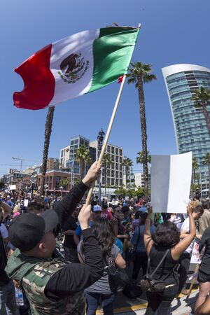 oppose: SAN DIEGO, USA - MAY 27, 2016: A man waves the Mexican national flag high over head before a crowd protesting the Trump campaign outside the San Diego Convention Center