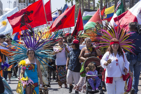 donald: SAN DIEGO, USA - MAY 27, 2016: Latinos celebrate their culture as women protesters march in traditional Aztec attire followed by a large crowd and flags representing Latin American countries outside a Trump rally in San Diego.