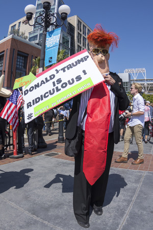 donald: SAN DIEGO, USA - MAY 27, 2016: A protester personifies hiimself as the ridiculous Donald Trump with a big red tie at an anti-Trump protest outside the San Diego Convention Center.