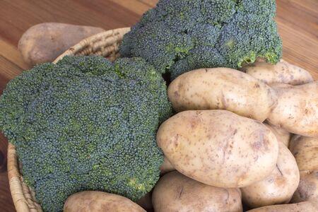 クローズ アップ不織布バスケットいっぱい新鮮な収穫のあずき色のポテトと木製のテーブルに緑 brocolli 写真素材 - 59566140