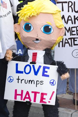 oppose: SAN DIEGO, USA - MAY 27, 2016: A Mexican pinata in the form of a smiling Donald Trump holds a sign reading Love trumps hate at a protest outside a Trump rally in San Diego.