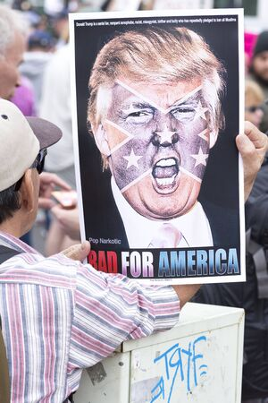 donald: SAN DIEGO, USA - MAY 27, 2016: A protester holds a sign featuring a picture of Donald Trump superimposed with the confederate flag at a protest outside a Trump rally in San Diego. Editorial