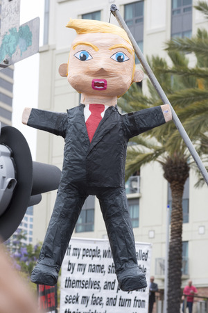 oppose: SAN DIEGO, USA - MAY 27, 2016: A pinata made in the likeness of Donald Trump hangs from a long pole at a protest outside a Trump rally in San Diego.