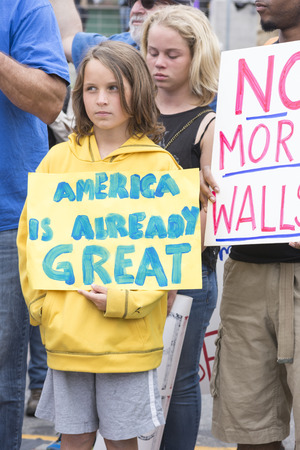 oppose: SAN DIEGO, USA - MAY 27, 2016: A young girl holds an America is Already Great sign at a protest outside a Trump rally in San Diego. Editorial