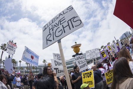 oppose: SAN DIEGO, USA - MAY 27, 2016: The Trump rally in San Diego attracts a huge crowd of protesters many of them carrying pro-immigrant signs such as this sign reading Illegals have rights. Editorial