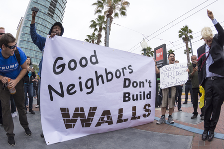 objection: SAN DIEGO, USA - MAY 27, 2016: Anti-Trump protesters display their opinion about the wall while a Trump fan smiles at their efforts during a protest outside a Trump rally in San Diego.