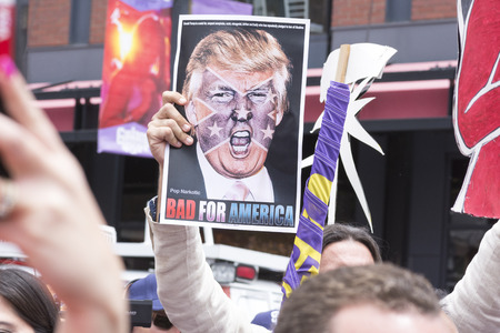 oppose: SAN DIEGO, USA - MAY 27, 2016: A protester holds a sign featuring an angry photo of Donald Trump and reading Bad for America at an anti-Trump protest outside a Trump rally in San Diego.