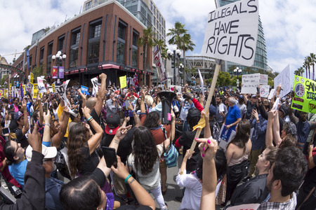 protest signs: SAN DIEGO, USA - MAY 27, 2016: The Trump rally in San Diego attracts a huge opposition crowd that gathers in front of the convention center in an emotionally charged protest to stop Donald Trump.