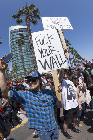 joins: SAN DIEGO, USA - MAY 27, 2016: A white American man holds a sign profanely rebuking Donald Trumps promise to build a wall as he joins other protesters outside a Trump rally in San Diego.