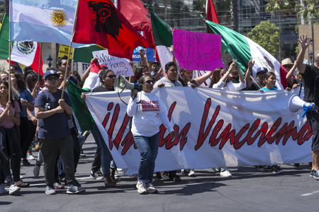oppose: SAN DIEGO, USA - MAY 27, 2016: Hispanics against Donald Trump march behind a banner of unity outside a Trump rally in San Diego. Editorial