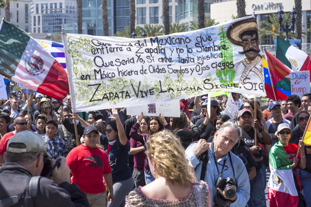 donald: SAN DIEGO, USA - MAY 27, 2016: A huge crowd gathers to march at an anti-Trump protest in San Diego while carrying a large banner in memory of the revolutionary Emiliano Zapata.