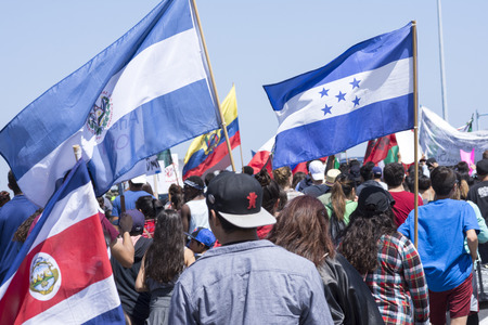 oppose: SAN DIEGO, USA - MAY 27, 2016: Protesters gather to march against Donald Trump outside a Trump rally in San Diego while carrying flags from Costa Rica, El Salvador, Honduras and other Central American nations.