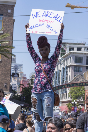oppose: SAN DIEGO, USA - MAY 27, 2016: An Afro American woman holds high a sign reading We are all women at an anti-Trump protest outside a Trump rally in San Diego. Editorial