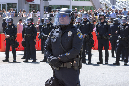 riot: SAN DIEGO, USA - MAY 27, 2016: San Diego police officers stand in riot gear at an anti-Trump demonstration outside a Trump rally at the San Diego Convention Center.