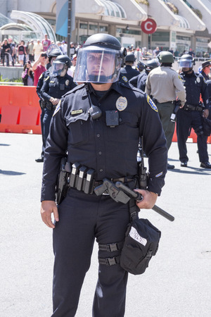 mace: SAN DIEGO, USA - MAY 27, 2016: A San Diego police officer stands ready in riot gear at an anti-Trump demonstration outside a Trump rally at the San Diego Convention Center.