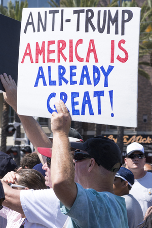oppose: SAN DIEGO, USA - MAY 27, 2016: A Caucasian man holds an anti-Trump sign amidst a huge crowd of protesters outside a Trump rally at the San Diego Convention Center