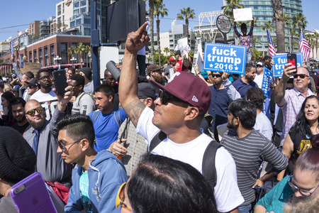 oppose: SAN DIEGO, USA - MAY 27, 2016: Among a huge anti-Trump crowd a protester displays the vulgar middle finger at a group of Trump supporters outside a Trump rally at the San Diego Convention Center. Editorial