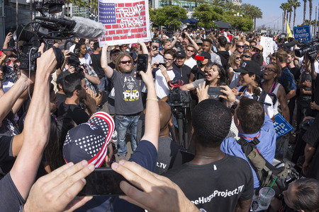 clash: SAN DIEGO, USA - MAY 27, 2016: Huge groups of protesters clash with Trump supporters in a verbal exchange outside a Trump rally at the San Diego Convention Center.