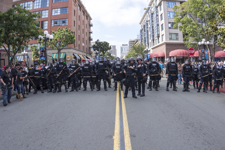 police unit: SAN DIEGO, USA - MAY 27, 2016: Riot police in full riot gear stand in position ready to march down San Diegos Fifth Avenue to disperse a crowd of hundreds of protesters and Trump supporters outside a Trump rally.