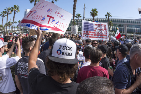 SAN DIEGO, USA - MAY 27, 2016: A man wearing a vulgar anti-Obama hat holds a sign promoting Donald Trump amidst a huge crowd of supporters vs. protesters outside a Trump rally at the San Diego Convention Center. Redakční