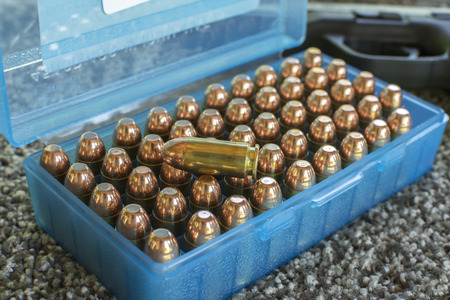 One shiny bullet lies on top of case of fifty copper bullets with brass cases